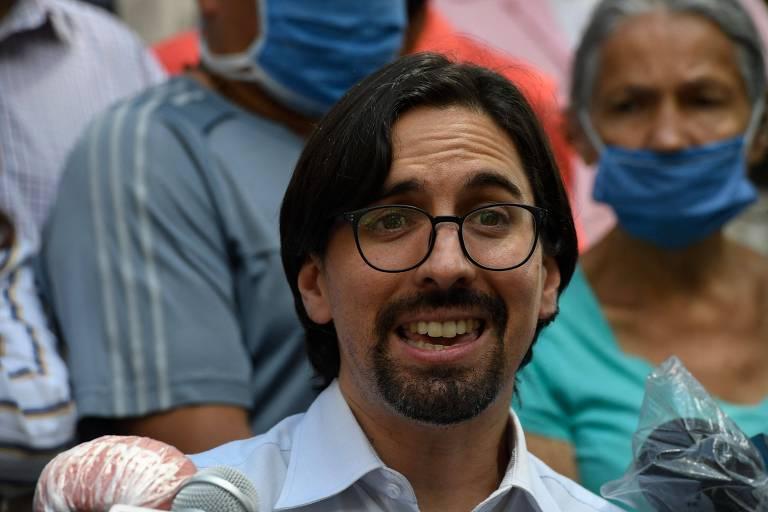 Homem de barbicha e óculos, com pessoas ao fundo
