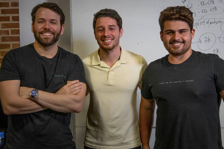 Três homens de camiseta, sorrindo