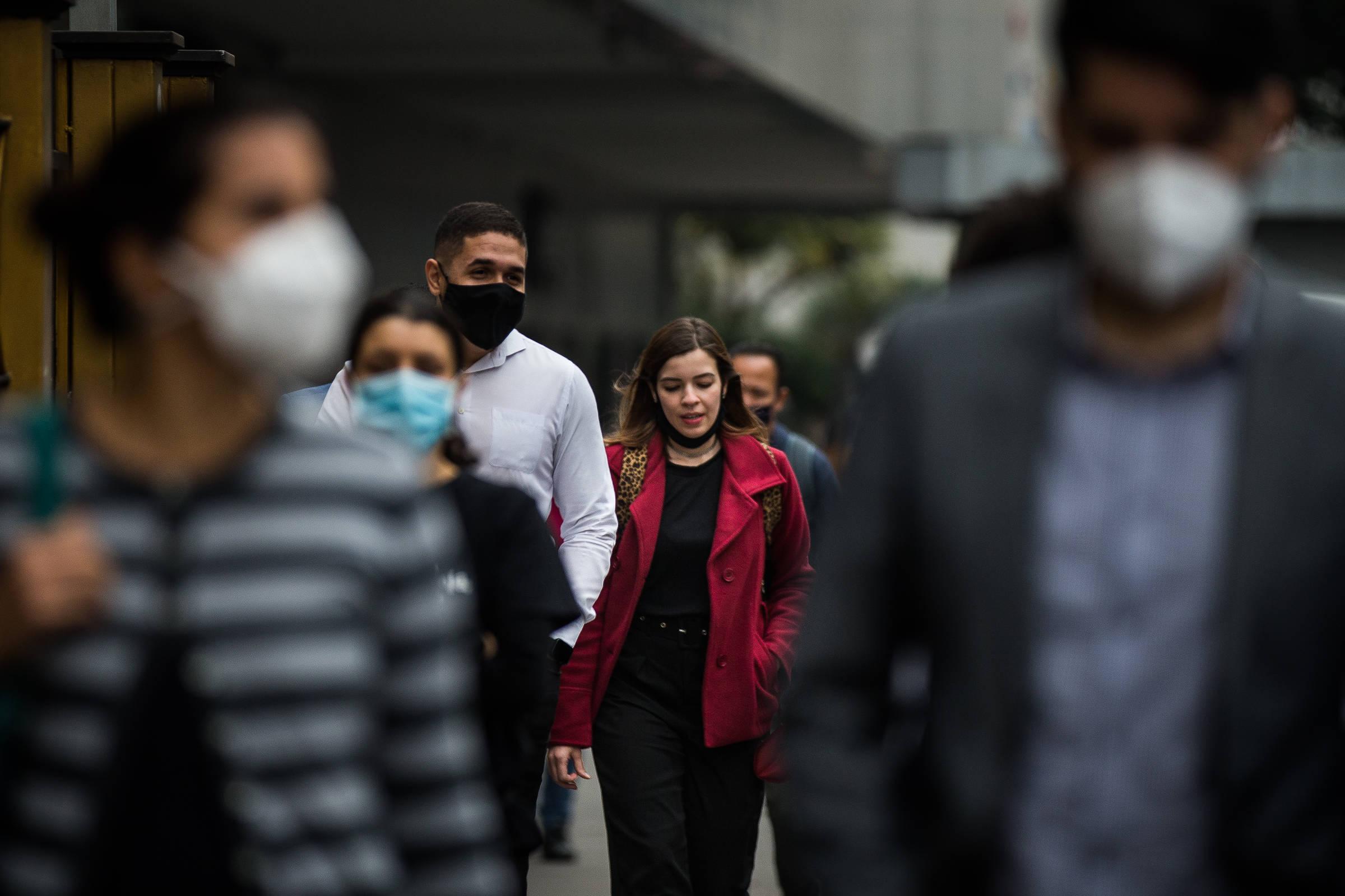 Pessoas andam pela avenida Paulista com roupas de frio