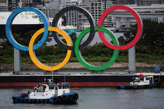 Boats prepare to tow giant Olympic rings as they are removed from the waterfront area at Odaiba Marine Park in Tokyo