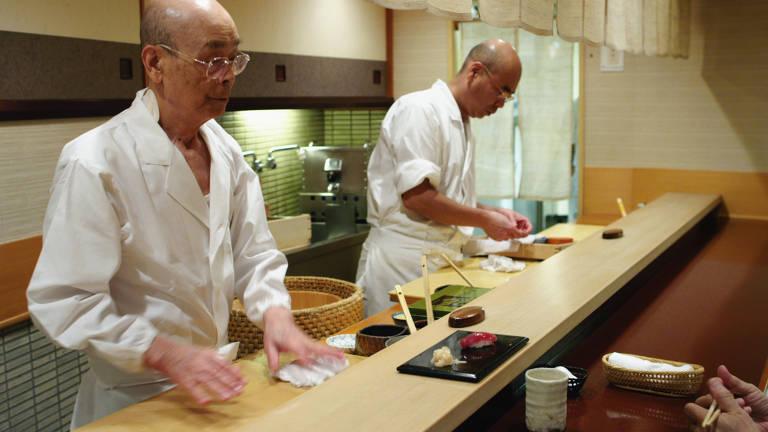 dois homens japoneses fazem sushis em bancada de madeira