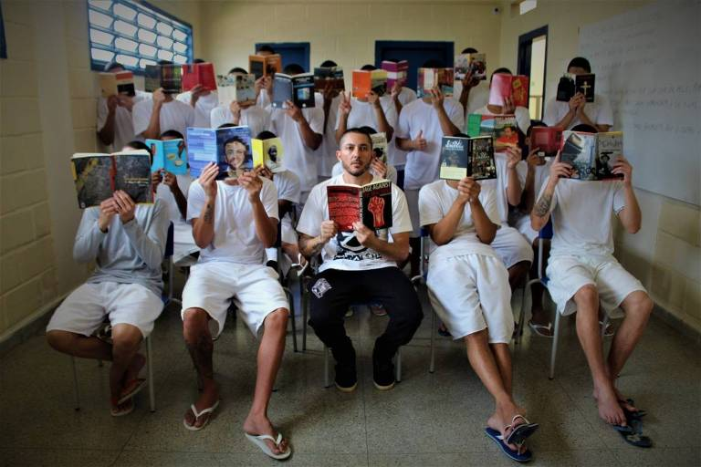 Professor se senta com livro em mãos na frente de uma fileira de alunos com livros abertos cobrindo seus rostos