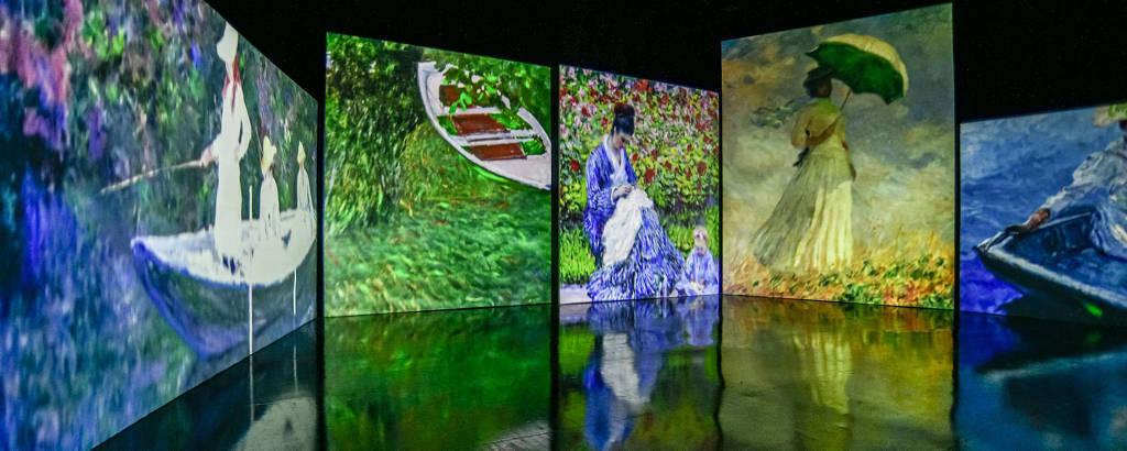 Em um ambiente escuro, cinco pinturas de Monet estão dispostas uma ao lado da outra, em telas digitais