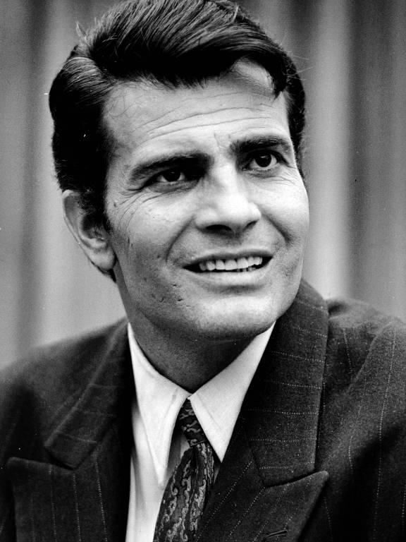 Foto em preto e branco de Tarcísio Meira, usando terno e gravata e sorrindo