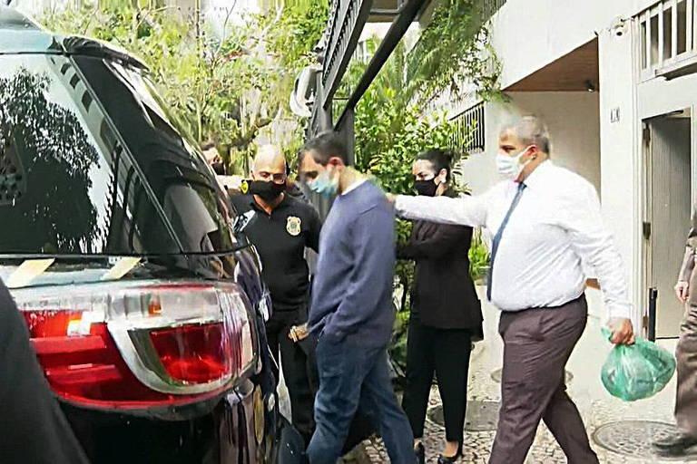 O então secretário de Administração Penitenciária do Rio, Raphael Montenegro (de máscara e blusa azul), é preso em sua casa na Urca