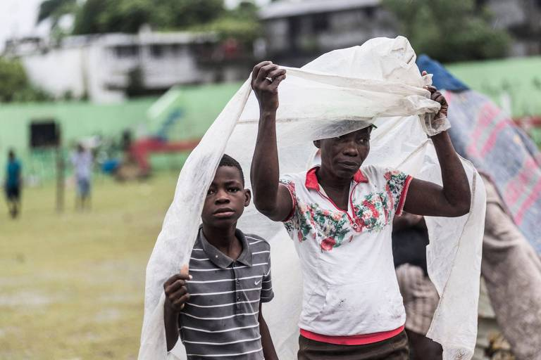 Haitianos em Les Cayes se protegem de chuva após a passagem da tempestade tropical Grace