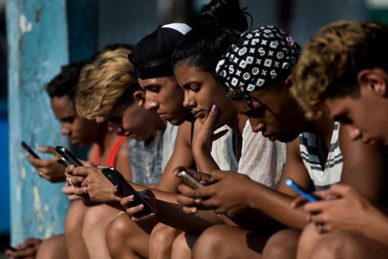 Jovens usam celular para se conectar à internet em Havana