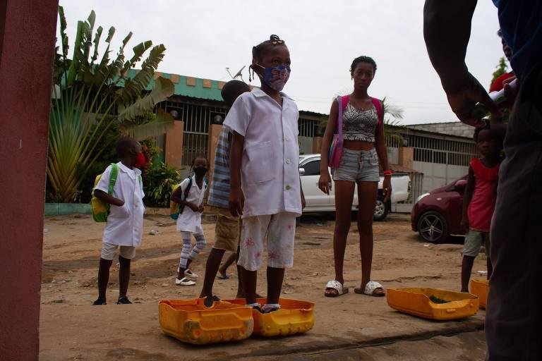 Estudante de Angola desinfecta os tênis antes de entrar em uma escola da capital, Luanda, que foi reaberta em fevereiro, após 11 meses fechada