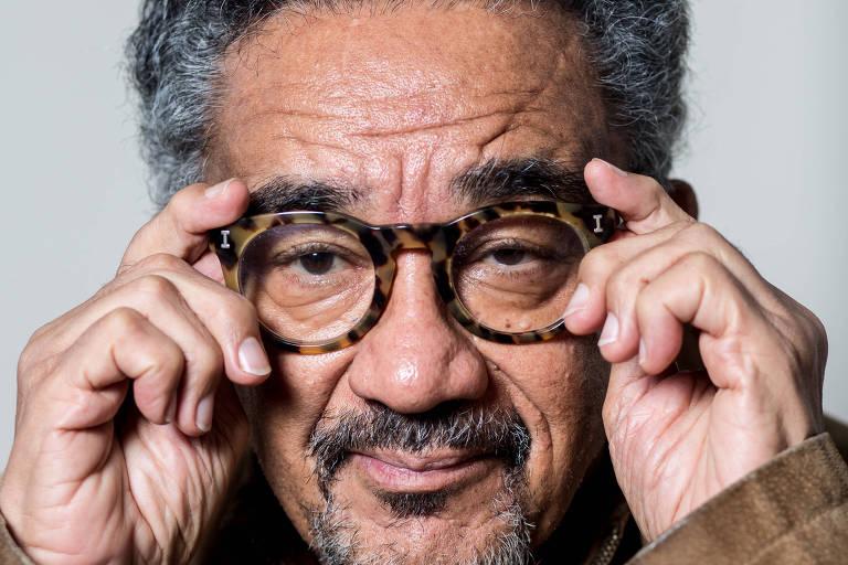 retrato do rosto de homem de cabelos crespos grisalhos , com óculos de aros grossos. ele não sorri e segura os óculos no rosto com as duas mãos