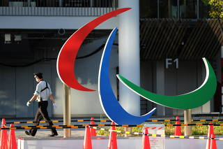 A security guard wearing a protective mask walks past the symbol of the Paralympic Games, in Tokyo