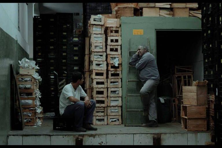 Homem sentando conversa com outro que esté em pé, ao lado de caixas