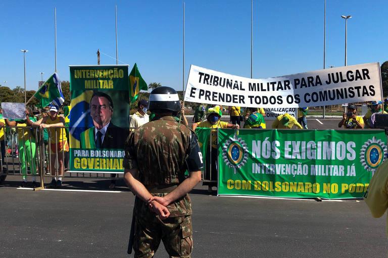 Homem de costas para a câmera observa manifestantes atrás de grade com cartazes e faixas
