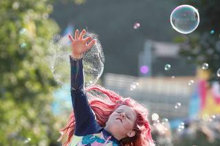 A young festivalgoer jumps to burst a bubble at Latitude Festival at Henham Park