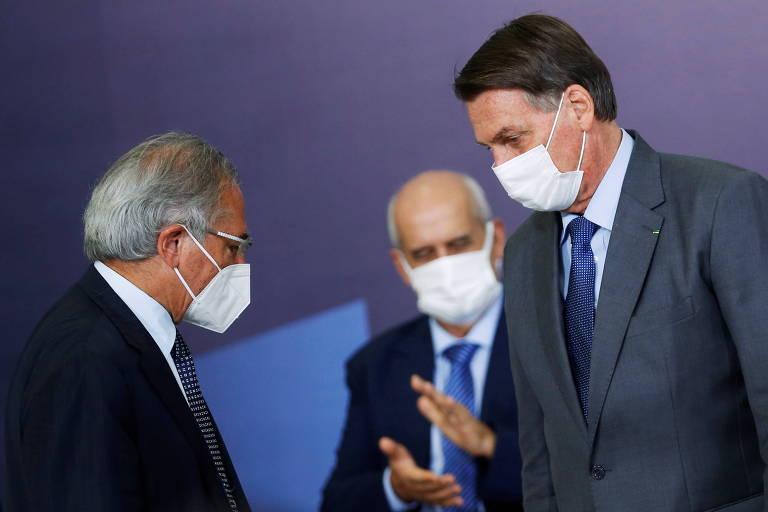 O ministro da Economia, Paulo Guedes (esq.), ao lado do presidente Jair Bolsonaro, ambos de terno e de pé, em evento em Brasília