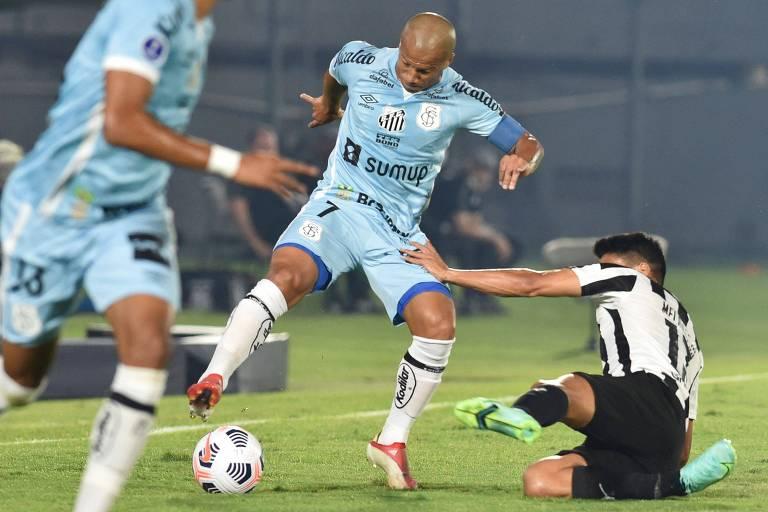 Carlos Sánchez, do Santos, tenta passar por marcação do Libertad, em jogo da Copa Sul-Americana