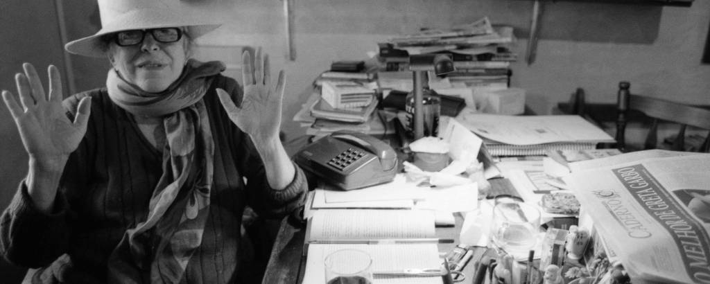 Hilda Hilst sentada, com as mãos levantadas e usando óculos e chapéu. Mesa com livros, jornais e papeis