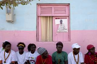Youth supporters of presidential candidate Jose Maria Vaz sit in front of his poster in Bissau