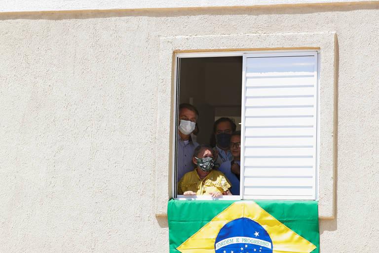 O presidente Bolsonaro, na janela de uma casa, em visita unidade habitacional em Juazeiro do Norte (CE)
