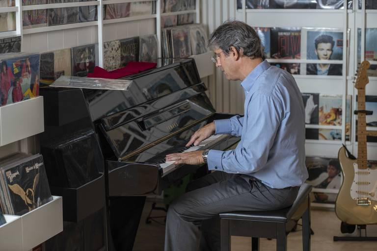 Homem branco veste camisa e calça e toca piano de armário preto