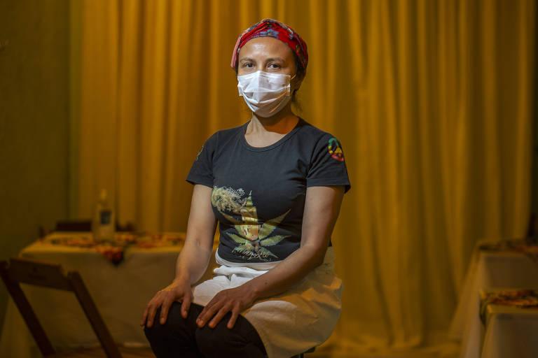 Foto mostra a  chef Edivan Maria dos Santos, 44, dona do bar e restaurante Oca da Quenquem, que via da porta de entrada o vaivém de pedestres, muitos deles sem máscara, na Vila Madalena, bairro boêmio de São Paulo