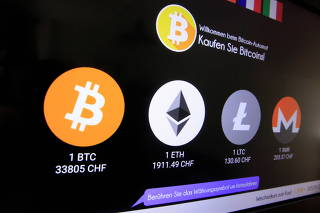 Exchange rates and logos of Bitcoin, Ether, Litecoin and Monero are seen on a cryptocurrency ATM in Zurich