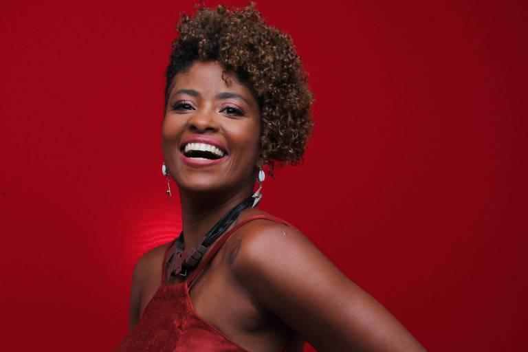 Mulher negra sorrindo e usando roupas vermelhas