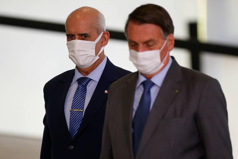 O ministro Ramos observa Bolsonaro antes de solenidade no Palácio do Planalto