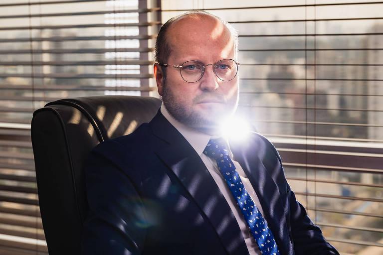 Homem de terno sentado em cadeira de escritório em frente a janela