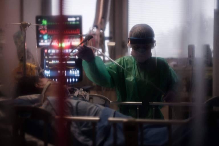 Profissional de saúde cuida de pessoa internada com Covid, com suporte de respiração, em hospital de Yokohama, no Japão