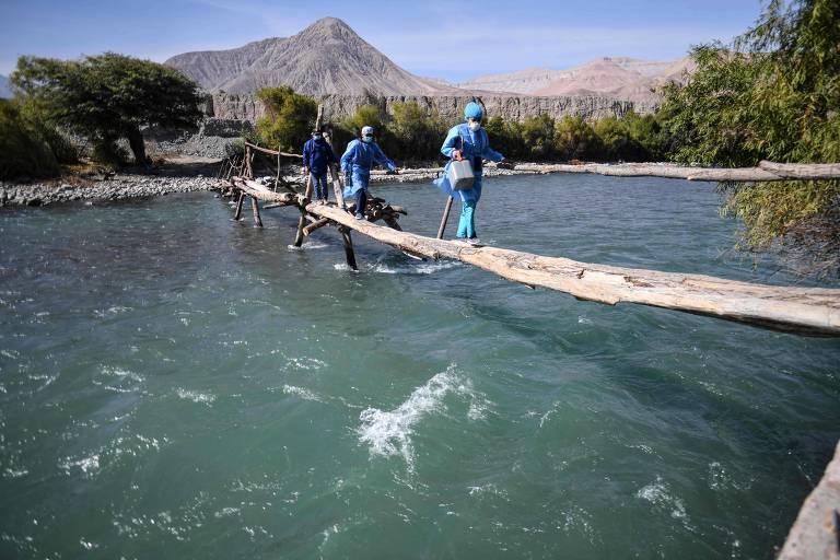 Profissionais de saúde cruzam ponte próxima de Arequipa, no Peru, para aplicar vacinação contra Covid em área remota; país é o que mais sofre com a lambda
