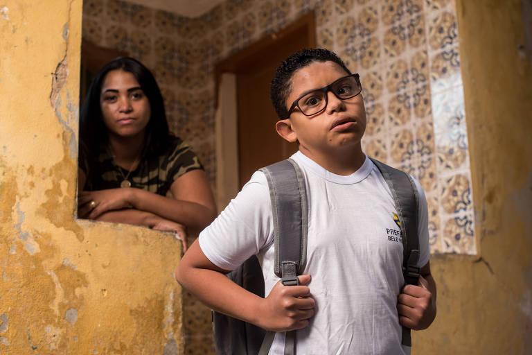 aluno de óculos, uniforme e mochila, com mãe ao fundo