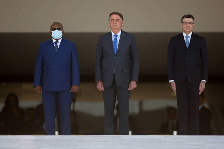 O presidente Jair Bolsonaro, acompanhado do ministro das Relações Exteriores, Carlos França (na direta da foto), recebe o presidente da Guiné-Bissau, Umaro Sissoco Embaló (à esquerda de Bolsonaro), no Palácio do Planalto, durante visita de estado. Todos estão de terno e apenas Embaló tem o nariz e boca cobertos por uma máscara