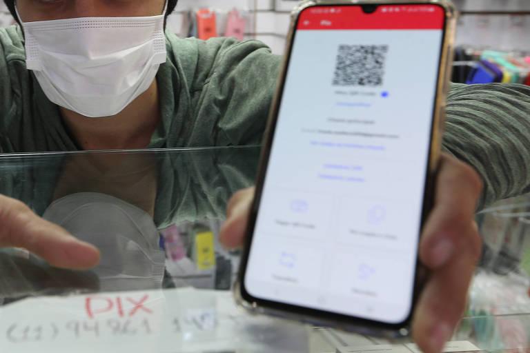 detalhe de mão de mulher com celular e transferência via Pix