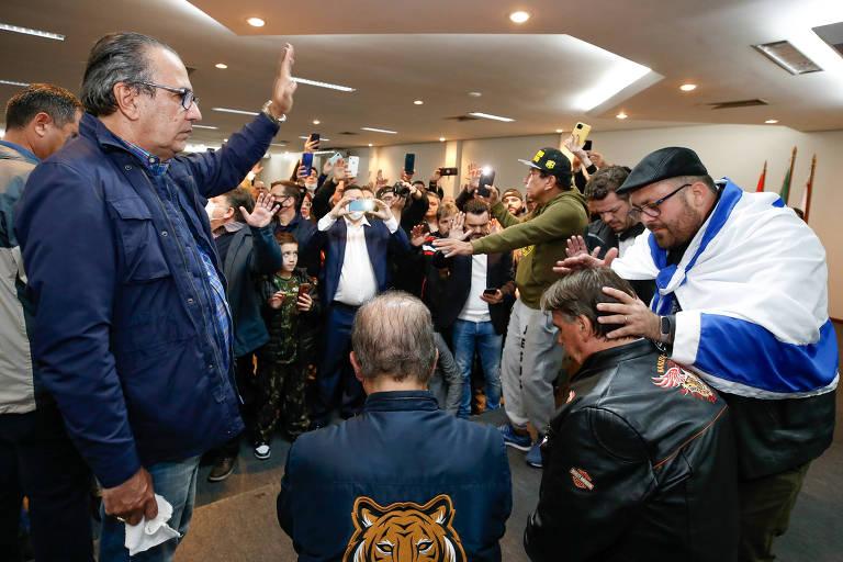 Em destaque, Jair Bolsonaro está de costas, ajoelhado, enquanto recebe orações do pastor Silas Malafaia em uma sala; ao fundo, pessoas assistem ao momento aglomeradas