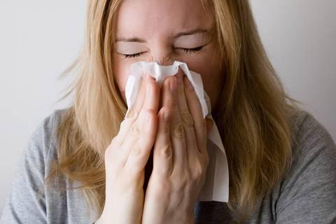 Espirro - Web Stories - Por que espirramos? - Mulher espirrando com lenço