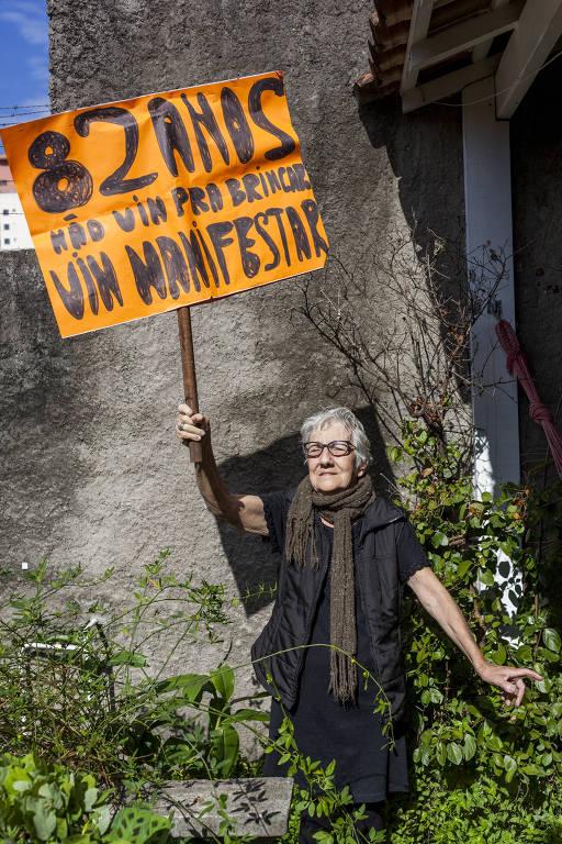 """mulher idosa está em quintal com plantas e segura cartaz em que se lê """"82 anos, não vim pra brincar, vim manifestar"""""""