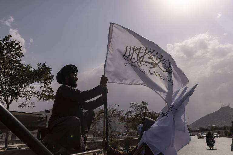 Militante do Talibã estende bandeira do grupo extremista em Cabul, capital do Afeganistão