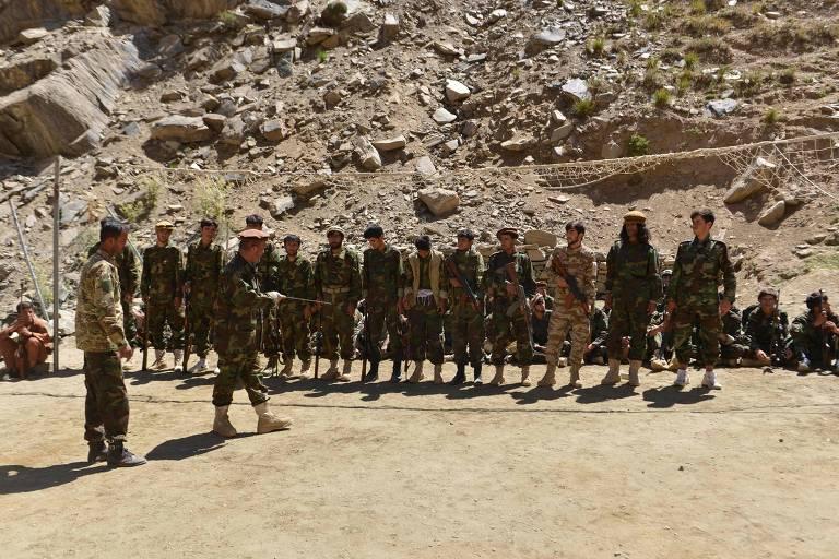 Grupo de combatentes fardados enfileirados escuta ordens do comandante