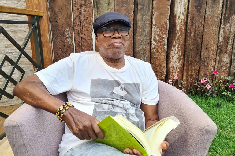 Cantor Milton Nascimento de boina, sem tranças, sentado com um livro