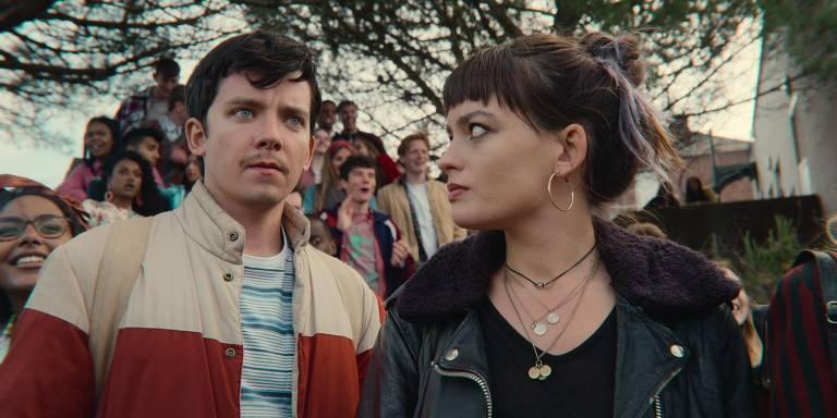 Um menino olha sério para frente enquanto uma menina olha séria para ele