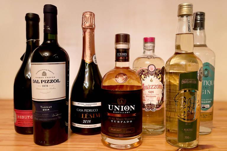 Garrafas de bebidas alcoolicas em cima de mesa de madeira
