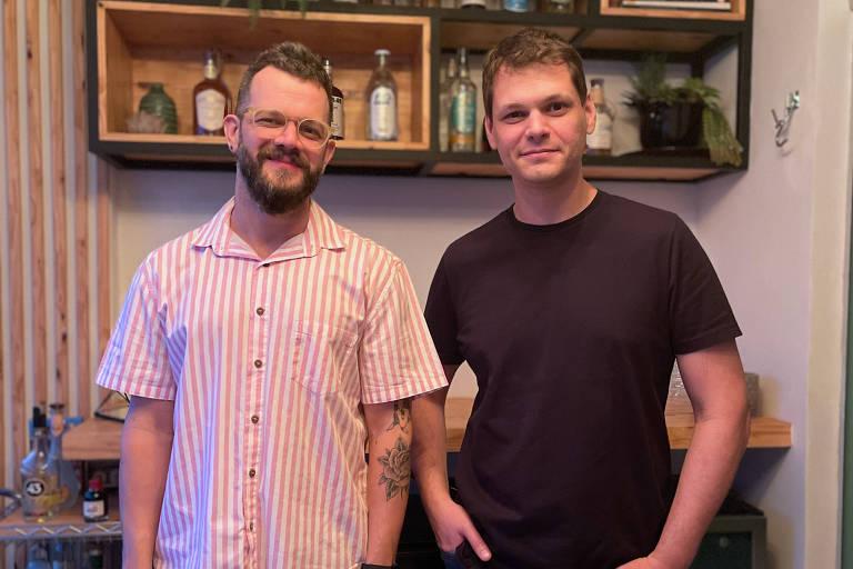 Dois homens brancos olham para camera