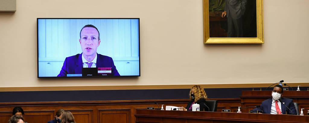 Mark Zuckerberg aparece de terno em uma televisão, ao lado de um púlpito de madeira com duas pessoas