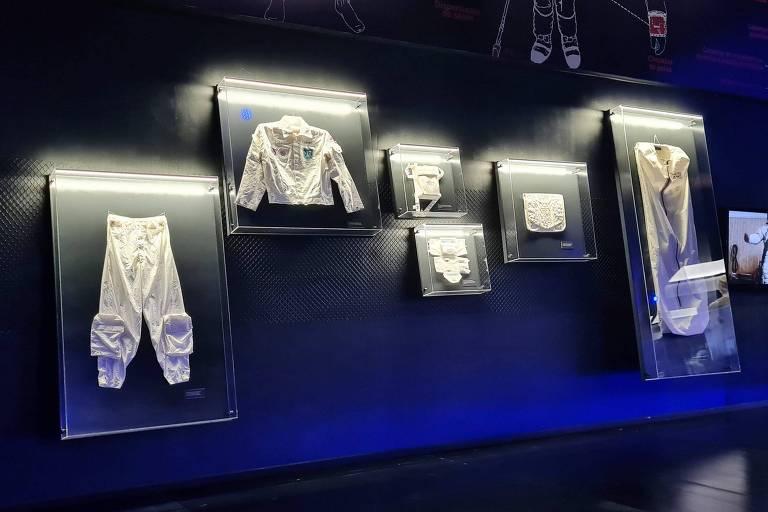 Parede azul mostra caixas transparente com peças de vestuário de brancas utilizadas por astronautas.