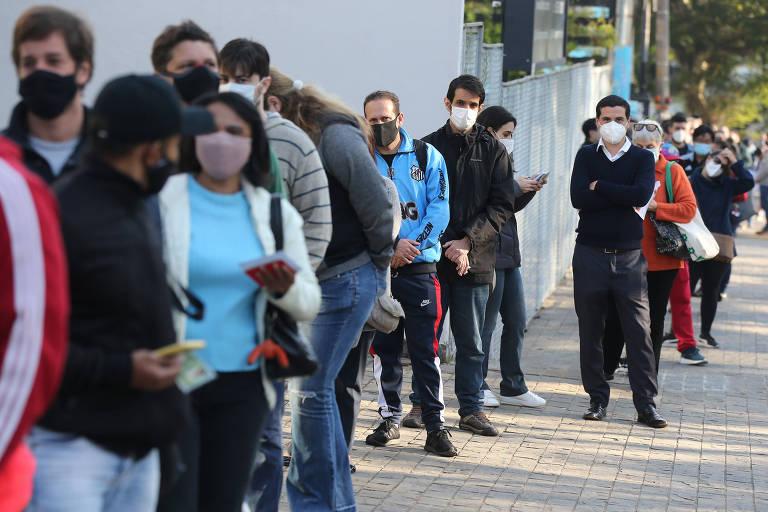 Pessoas em fila na calçada, de máscara