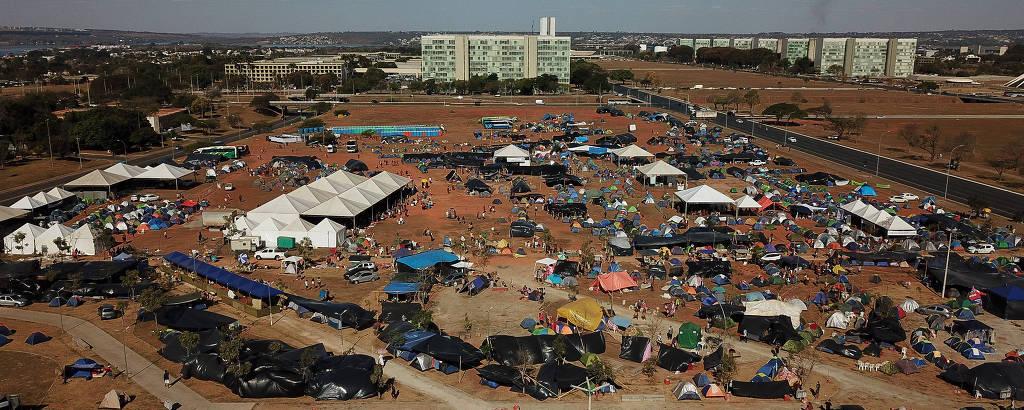 Vista aérea mostra pequenas tendas que se espalham em planície aberta, com edifícios ao fundo