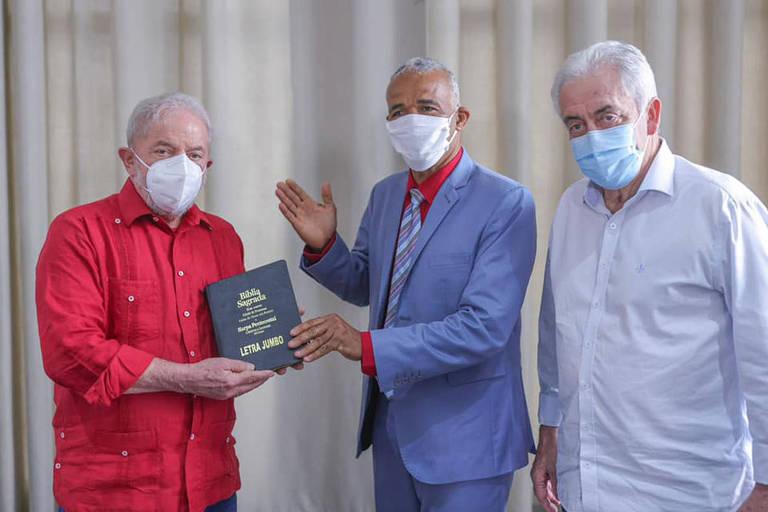 Homem entrega um exemplar da Bíblia a outro homem enquanto um terceiro assiste