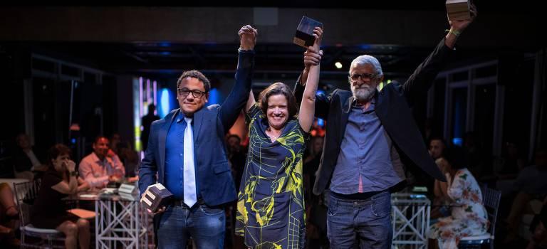 três pessoas, sendo uma mulher no centro e dois homens ao seu lado, erguem as mãos felizes por receber prêmio
