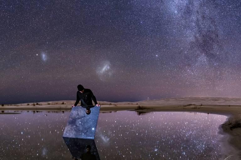 Homem usando casaco e toca segura um espelho sobre uma poça de água. Constelações aparecem sobre ele por todo o céu e são refletidas no espelho e na água. Ao fundo, bancos de areia compõem a paisagem.