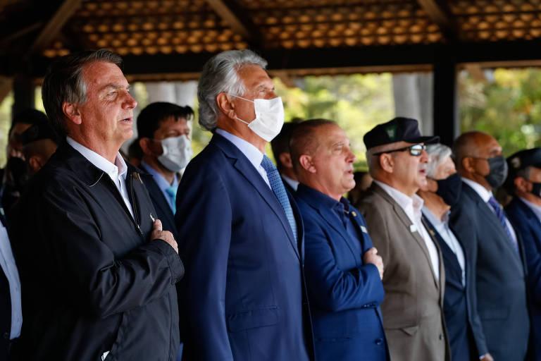 Jair Bolsonaro leva a mão ao peito durante o canto do Hino Nacional, ao lado de outros homens